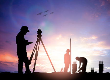 teodolito: ingeniero encuesta silueta trabajando en una obra de construcción más trabajador de la construcción borrosa en el sitio de construcción