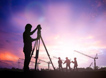 tools construction: ingeniero encuesta silueta trabajando en una obra de construcci�n m�s trabajador de la construcci�n borrosa en el sitio de construcci�n