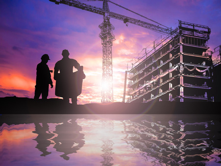 building tool: silhouetteengineer working  in a building site over Blurred construction worker on construction site Stock Photo