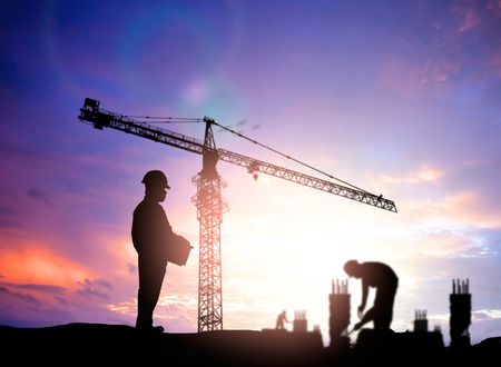 housing industry: silhouette engineer looking blurred construction worker on construction site Stock Photo