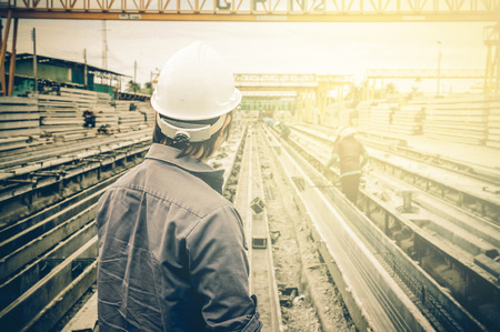 Engineer looking at construction site over Blurred construction worker on construction site.