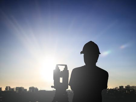 ingeniero: silueta encuesta hombre negro e ingeniero civil opere en un lugar de trabajo en una obra de construcción sobre tierra trabajador de la construcción en la puesta del emplazamiento de la obra. examen, inspección, encuesta