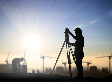civil construction: silhouette black man survey and civil engineer stand on ground working in a land building site over Blurred construction worker on construction site. examination, inspection, survey Stock Photo