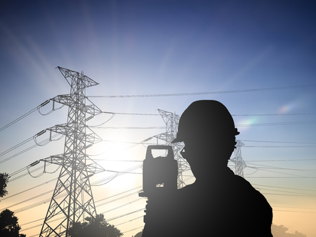 land scape: Silhouette Successful male engineer standing survey work on construction over blurred high-voltage pylons and construction. examination, inspection, survey, Industrial Land Scape