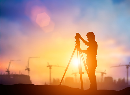 La silueta del joven ingeniero normas de construcción que trabaja en línea con el medio ambiente mundial de la construcción y el medio ambiente en todo el sitio de trabajo. más trabajador de la construcción en la puesta del emplazamiento de la obra