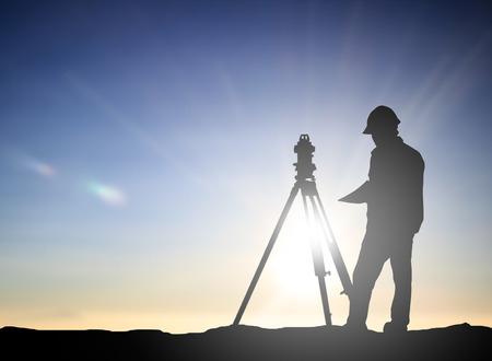 silueta encuesta hombre negro e ingeniero civil opere en un lugar de trabajo en una obra de construcción sobre tierra trabajador de la construcción en la puesta del emplazamiento de la obra. examen, inspección, encuesta