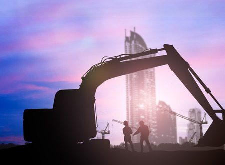 loaders: silhouette Loaders and construction worker in a building site over Blurred construction site