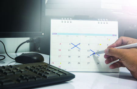 young businessman holding a pen to write on the calendar date