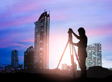 silhouette survey engineer working  in a building site over Blurred construction worker on construction site 版權商用圖片 - 56176413