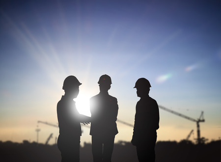 silhouette three back people engineer talking Business  in a building site over Blurred construction site