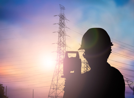 geodesy: Silhouette Successful male engineer standing survey work on construction over blurred high-voltage pylons and construction. examination, inspection, survey