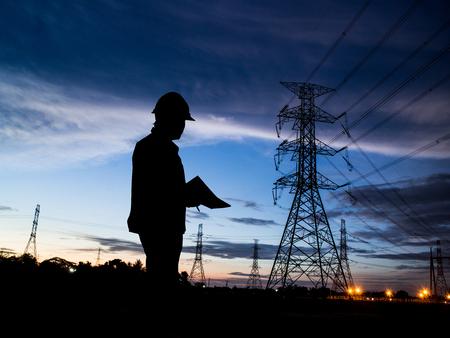 electricidad industrial: silueta del hombre de ingenieros de pie en la estación de electricidad a través de energía eléctrica borrosa Foto de archivo