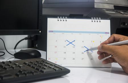 punctuality: Hombre de negocios joven que sostiene una pluma para escribir en la fecha del calendario de la reuni�n mensual. Calendario lata vac�a para llenarla. Conceptual de la puntualidad, la estrategia, la visi�n o la educaci�n.