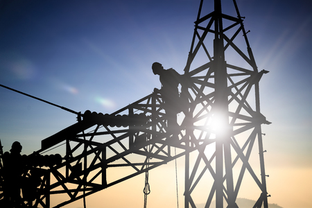 over voltage: Silhouetteblack man  electrical engineer and electrical workers are installing high voltage systems over blur night city