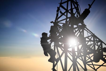 electricidad industrial: Silhouetteblack hombre ingeniero eléctrico y los trabajadores eléctricos están instalando sistemas de alto voltaje sobre el desenfoque de la noche de la ciudad