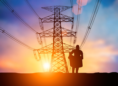 over voltage: silhouette The young engineer was thinking to comply with environmental, construction and the environment around us and have a minimal impact on the public  over Blurred Pole high voltage transmission lines Stock Photo