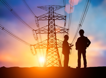 comply: silhouette The young engineer was thinking to comply with environmental, construction and the environment around us and have a minimal impact on the public  over Blurred Pole high voltage transmission lines Stock Photo