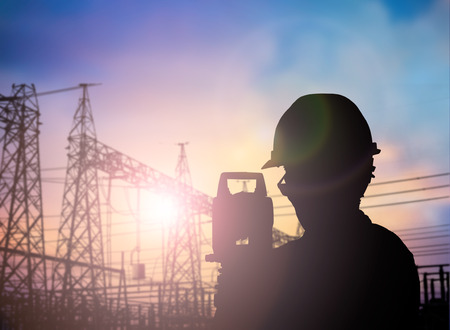 over voltage: Silhouette Successful male engineer standing survey work on construction over blurred high-voltage pylons and construction. examination, inspection, survey
