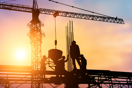 Trabajadores de la construcción y los ingenieros que trabajan en alta seguridad cerca de la torre de la grúa. La industria pesada y Seguridad en el concepto de trabajo. Foto de archivo - 57270557