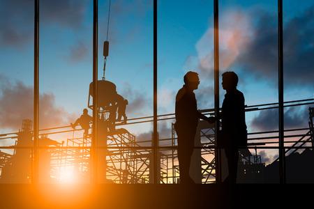 Succesvolle groei van de joint venture, vooruitgang en potentiële concepten. Silhouetmannen schudden elkaars hand om een deal te sluiten tussen bedrijven over wazige werknemers op Construction Site. Stockfoto