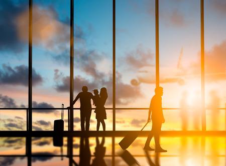 Junge Reisende schleppen Koffer, um im Busbahnhof ins Ausland zu reisen, würde das Land über unscharfe andere Reisende verlassen, die Flugzeug und Stadt bei Nacht innen mit großen Fenstern warten.