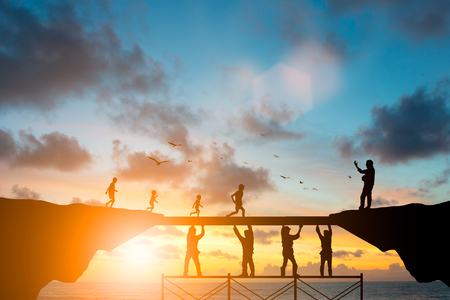 learning and teaching, teacher, team responsible for the idea of progress concept.Silhouette. Adults helped build the foundation for a child to grow up and grow efficiently over blurred natural. Stockfoto
