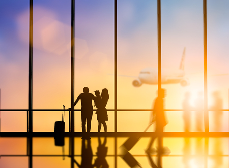 Young travelers dragging suitcases walked to travel abroad in the bus terminal would leave the country over blurred other travelers waiting plane and city at night interior with large windows. 版權商用圖片