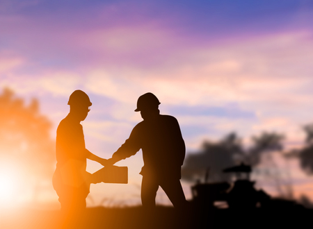 Silhouette engineer construction industry stands shake hands with the construction team and construction contract business in large farms over blurred pastel background sunset industry. Heavy industry concept.