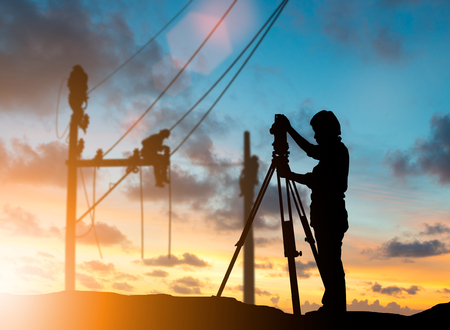 silhouette survey engineer working  in a building site over Blurred construction worker on construction site Stock Photo
