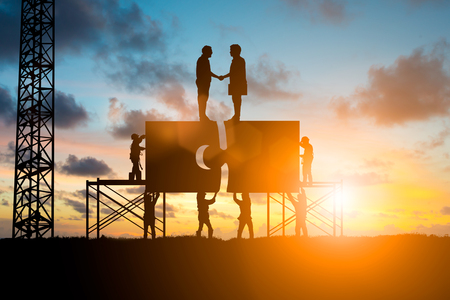 Silhouette Team business work connecting jigsaw puzzle piece together.the two organizations can work together more effectively over blurred sky.Teamwork potential and motivate employee growth concept Stock Photo