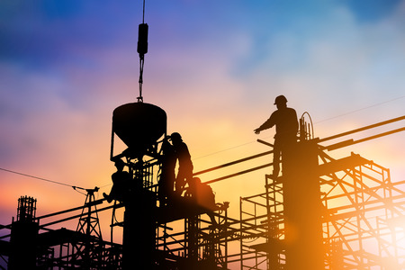 Silhouette Standing Orders of Engineers crane lifted the pickup up poured cement building over blurred pastel background .industry,Business, standards, training, specific, professional license, safety