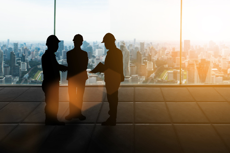 Ingénieur de silhouette Bonne affaire. Trois ingénieurs gens d'affaires se serrant la main sur le fond de ville floue pastel au coucher du soleil. concept de l'industrie lourde et sécurité au travail Banque d'images - 81957451