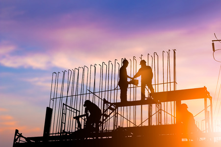 Silhouette engineer construction industry stands shake hands with the construction team and construction contract business over blurred pastel background sunset industry. Heavy industry concept. 版權商用圖片
