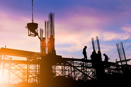 budgetary: Silhouette construction industry engineer standing orders for construction team to work safely on high ground over blurred background sunset pastel for industry background. heavy industry concept. Stock Photo