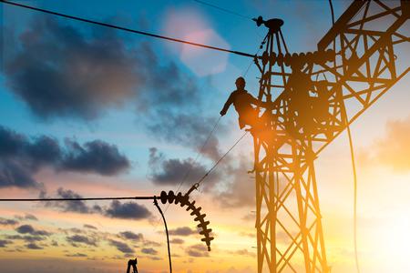 Silhouet elektricien werk installatie van hoogspanning in hoogspanningsstations veilig en systematisch over wazig natuurlijke achtergrond.