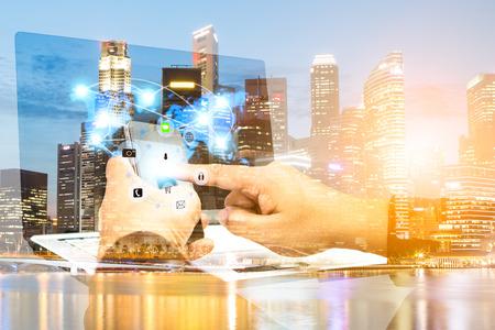 Business, communicatie, verbinding, technologie concept. Dubbele blootstelling zakenman met behulp van smartphone uploaden gegevens Business over wazig stad scape. Selecteer focus.flare licht