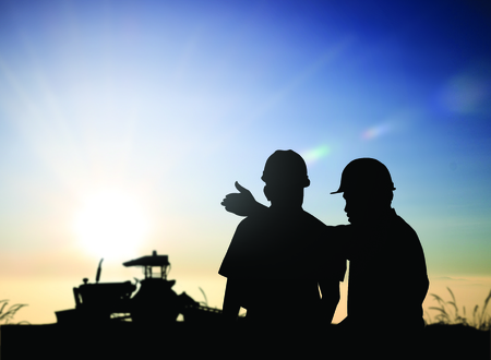silhouette man survey and civil engineer stand on ground working in a land building site over Blurred construction worker on construction site. examination, inspection, survey 版權商用圖片