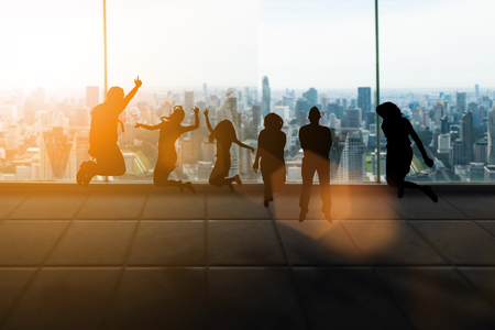 Silhouette group of business men and women happy jumping on sales or success. Business success achieved by teamwork and help each other to work over blurred nature. Business and Finance concept.