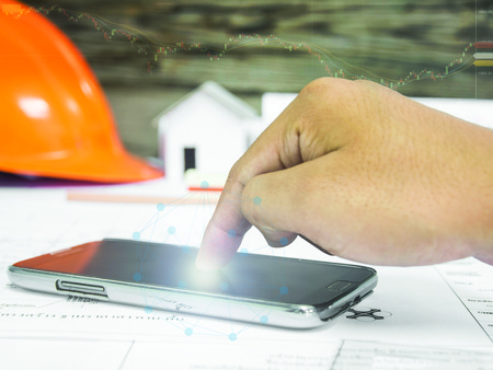 Hands on smart phones working with modern technology and digital layer effect over blurred architectural blueprint of office building and stock chart . business strategy concept