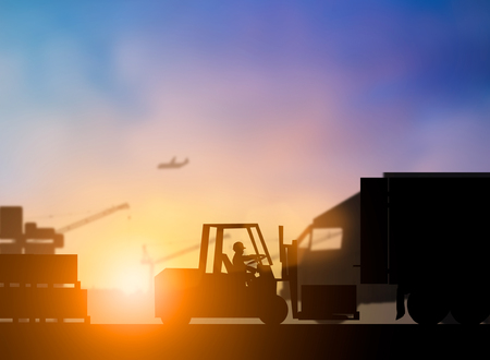 Silhouette driver of the truck was put in the car to transport cargo to customers, accurately and securely over blurred pastel background sunset shipping. Heavy industry and Transportation concept.