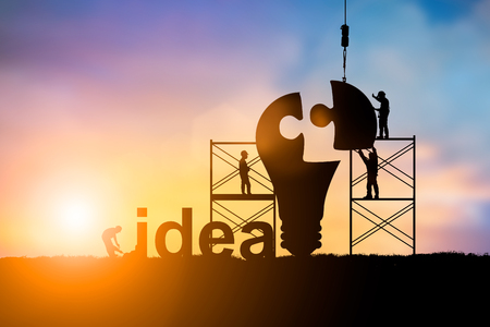 Silhouette Team business engineer work connecting jigsaw puzzle piece together. team responsible for the idea of progress over blurred natural.Teamwork potential and motivate employee growth concept Stock Photo