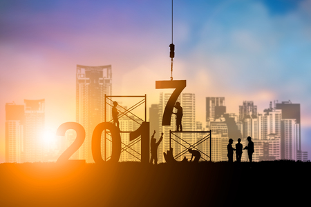 Silhouette employees work as a team to change the 6 to 7 prepared to welcome the New Year over blurred sunset. Teamwork, success, Industry, Business, People, engineers, working a systematic concept. 版權商用圖片