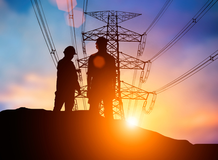 silhouette The young engineer was thinking to comply with environmental, construction and the environment around us and have a minimal impact on the public  over Blurred Pole high voltage transmission lines Stock Photo