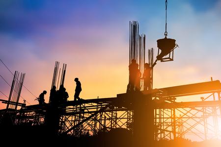 業界の背景に背景をぼかした写真夕日パステル上高地で安全に作業する建設チームのシルエット建設産業エンジニア立って注文。重工業の概念。 写真素材