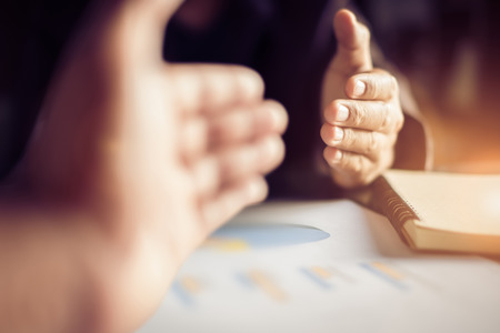 Business people handshake after meeting caption analyze graphs and goals set over blurred office.Film tones and Light fair