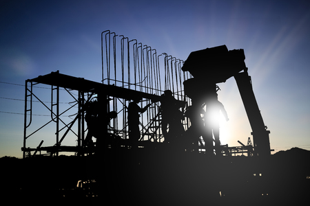 silhouetteConstruction workers work in preparation for binding rebar and concrete work. and the environment around the work site. over Blurred construction worker on construction site