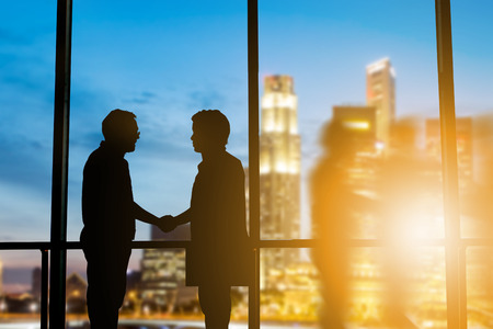 Success of the joint venture business growth, progress and potential concepts.Silhouette businessmen shake hands finishing a deal between businesses over blurred employees the city night.flare light