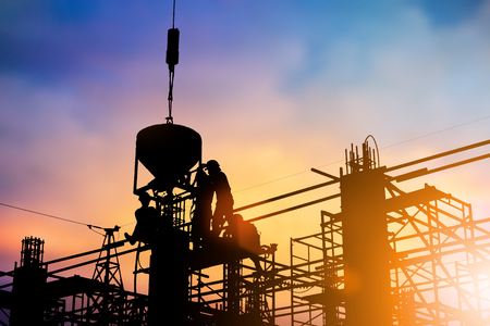Silhouette of construction workers to work safely on a high with the engineer in charge., construction or planned over blurred pastel background sunset industry. Heavy industry concept. Stock Photo