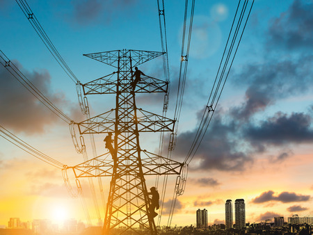 silhouette engineer repair and electrical installation work on high voltage pylons over Blurred construction site.CSR ESG Business on industry, People, Science, Technology, Transportation concept. Stock Photo