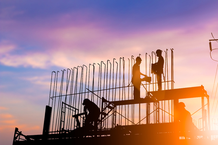 Silhouette construction industry engineer standing orders for construction team to work safely on high ground over blurred background sunset pastel for industry background. heavy industry concept. Stock Photo